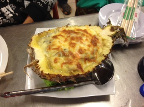 Seafood baked with cheese in pineapple